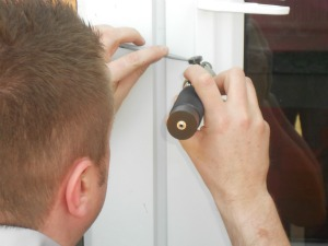 A locksmith working on a door